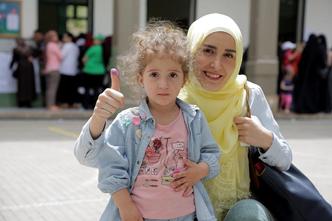 A woman shows off the electoral ink after voting in the parliamentary elections in Lebanon, with her daughter. Photo: UN Women/Jean Safi