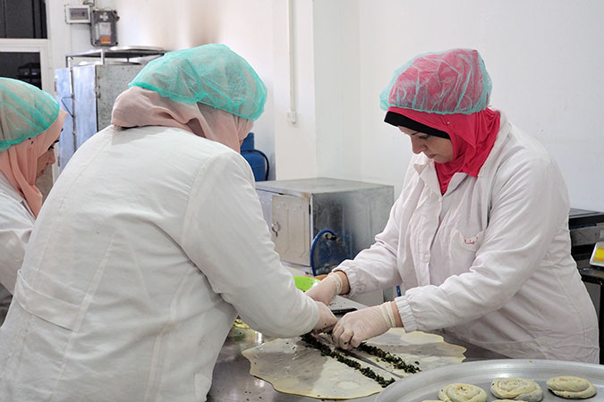 Lubna Masalha (right), a survivor of violence and a trainee at Food Incubator, making traditional Palestinian pastries. Photo: UN Women/Eunjin Jeong
