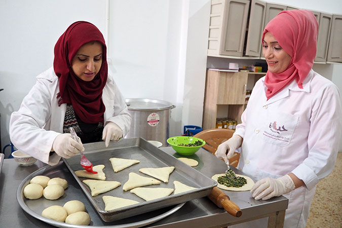 Mirvat Souri (right), a survivor of violence and a trainee at Food Incubator, listening to the instructor Samar Al-Nabahin explaining how to oil spinach staffed pastries. Photo: UN Women/Eunjin Jeong