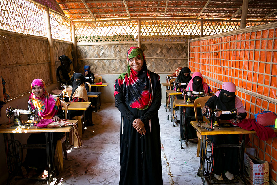 Noor Nahar stands in front of a classroom of Rohingya women refugees learning to sew in Cox's Bazar Bangladesh. Photo: UN Women/Allison Joyce