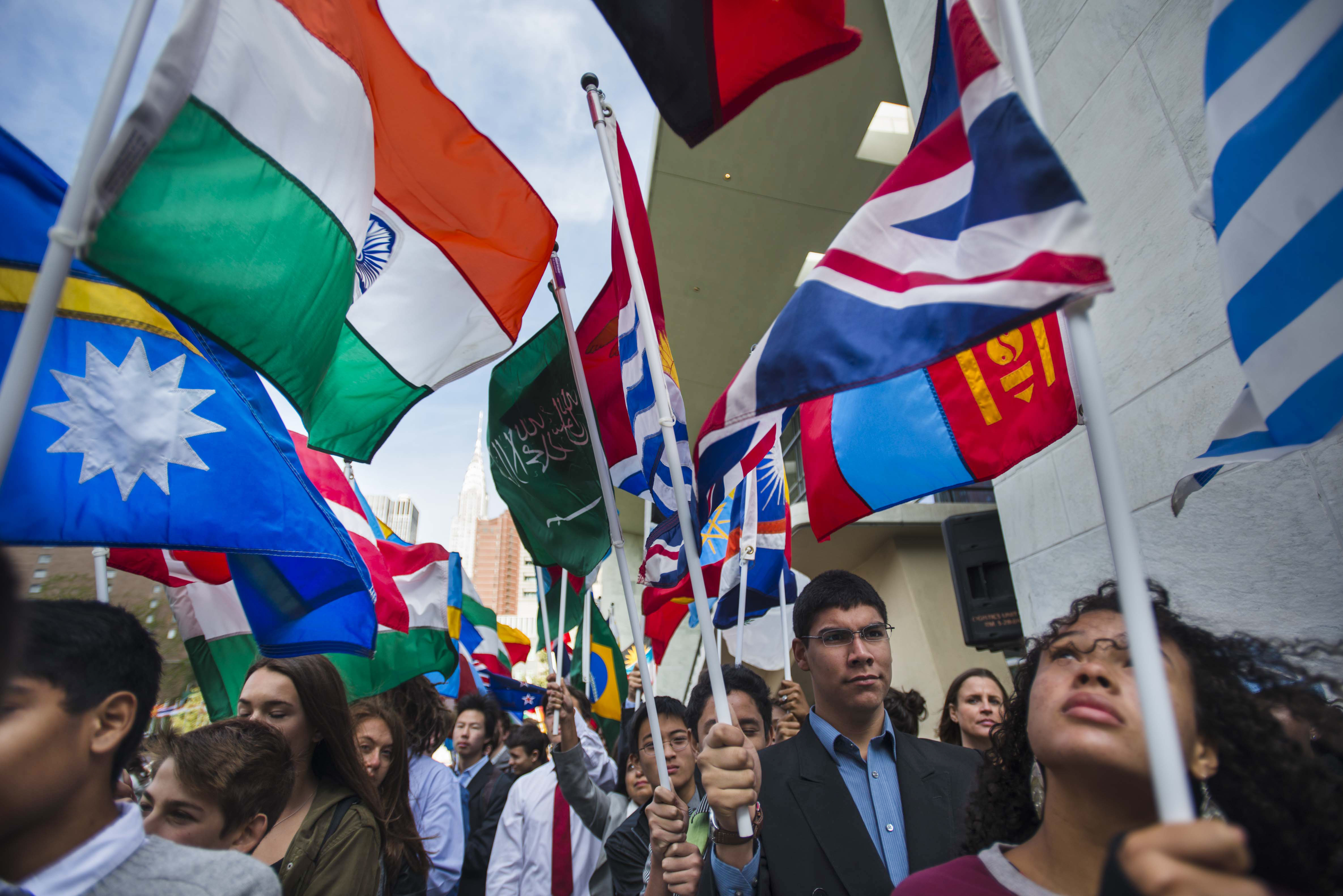 Students  carry  the  flags  of  United  Nations  Member  States  during  the  annual  Peace  Bell  Ceremony  held  in  observance  of  the  International  Day  of  Peace  (21  September),  ahead  of  the  70th  session  of  the  General  Assembly Photo: UN Photo/Amanda Voisard