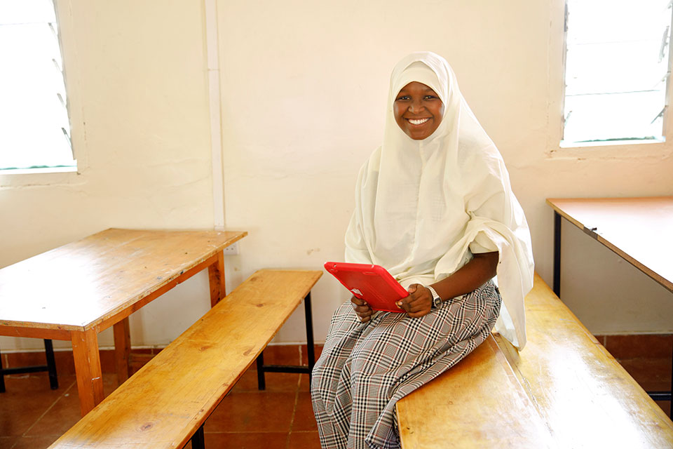 Mumina Khalif sits with a tablet computer in the classroom used for computer class and the ICT club. Photo: UN Women/Ryan Brown