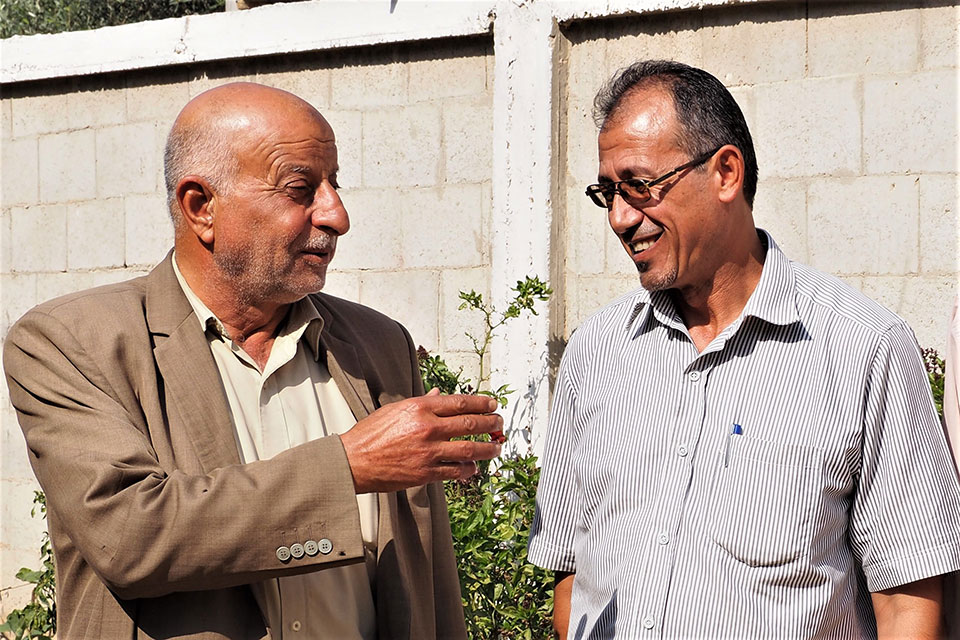 """Abdel Naser Abu Te'ema, the """"Muktar"""" and Wael Abu Ismael talking about the Muktar's decision to not approve marriage under 18 for both boys and girls. Photo: UN Women/Eunjin Jeong"""