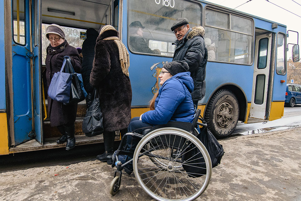Tetyana Bobrovska  waits for a city bus in Kramatorsk, Ukraine.  In Kramatorsk, despite recent improvements in infrastructure, many older buses and bus stop shelters are inaccessible to wheelchair users.   Photo: UN Women/Artem Hetman