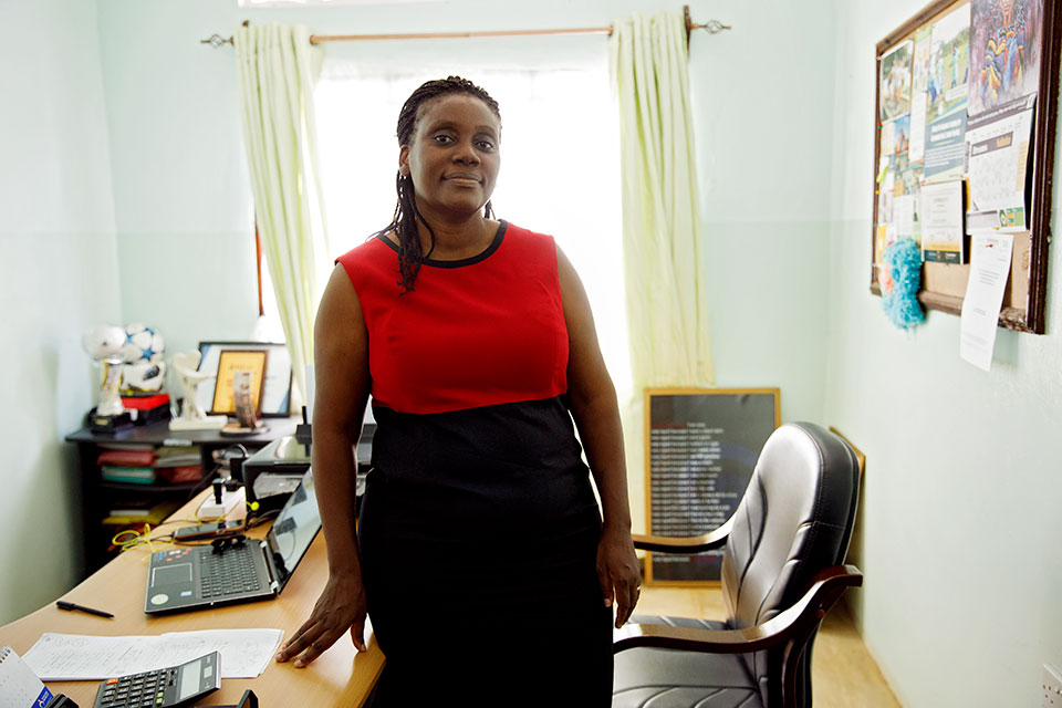 Dorcas Amakobe poses for a photo in her office. Photo: UN Women/Ryan Brown