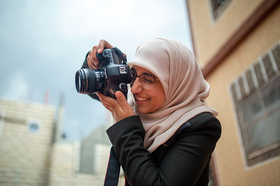 Doaa Eshtayeh taking a photo. Photo: UN Women/Carlos Pérez Osorio