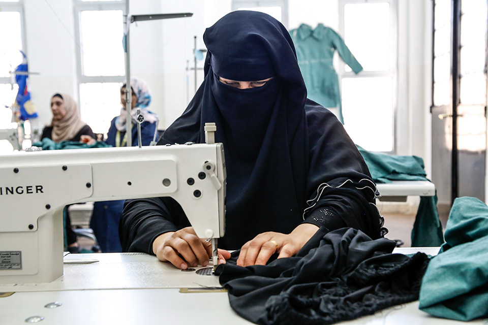 Mona Ahmed Alqkla, 39, has found an incentive-based volunteer opportunity as a tailor at the UN Women Oasis Centre in Taibeh. Photo: UN Women/Lauren Rooney