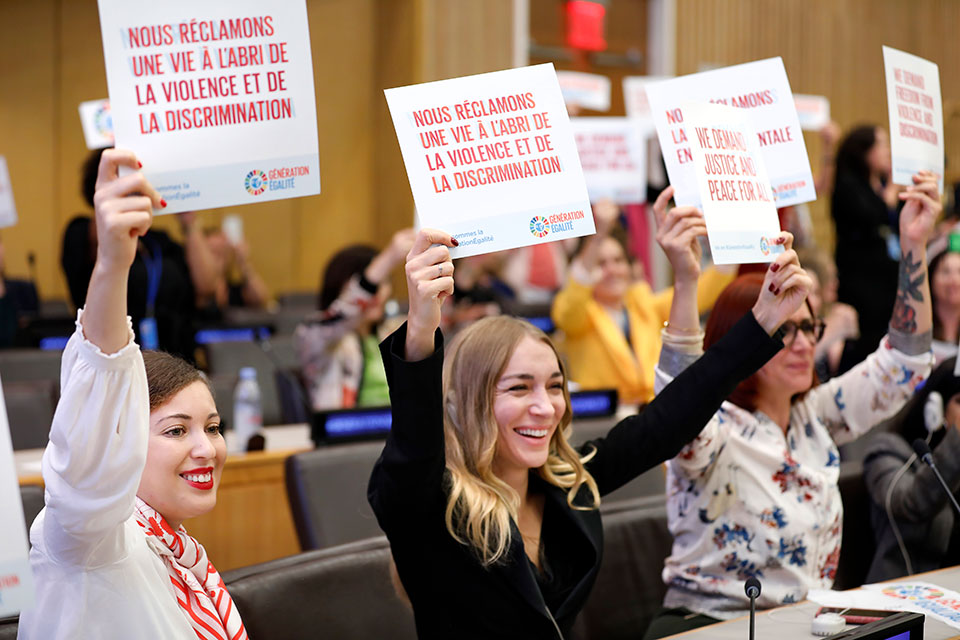 Attendees of the Gender equality: from the Biarritz Partnership to the Generation Equality Forum event hold up some of their gender equality demands.