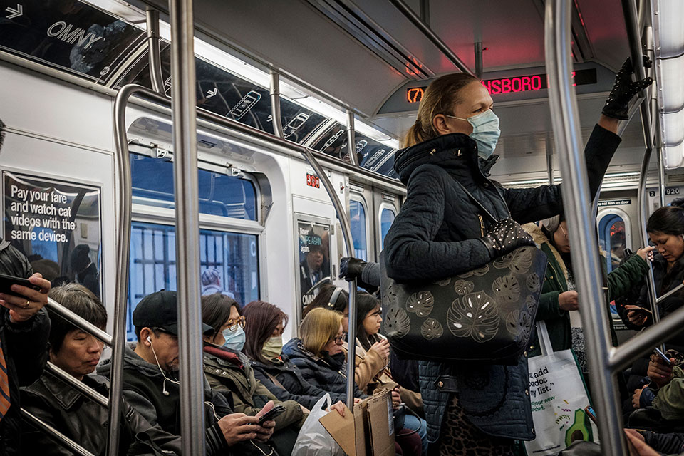 A women on public transit in New York wears face mask in March 2020, when many appear to be doing so as a precaution against COVID-19.  Photo: UN Photo/Loey Felipe