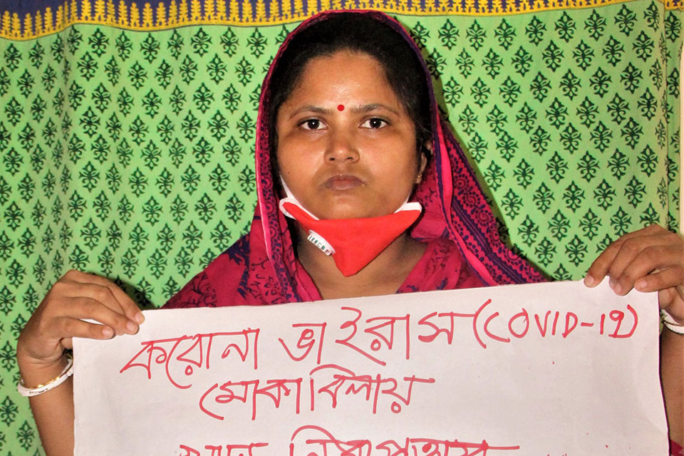 Rani Begum, domestic worker from Dhaka, is one of the many women in the informal economy who has lost work due to COVID 19.  She holds a sign calling for food security during the pandemic.  Credit: BNSK/Saad Sami