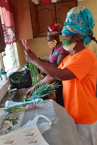 Women farmers package and label vegetables for sale at a member's home, as their factory construction was stalled due to COVID-19 restrictions on movement and work. Photo: UN Women/Dawn Francis