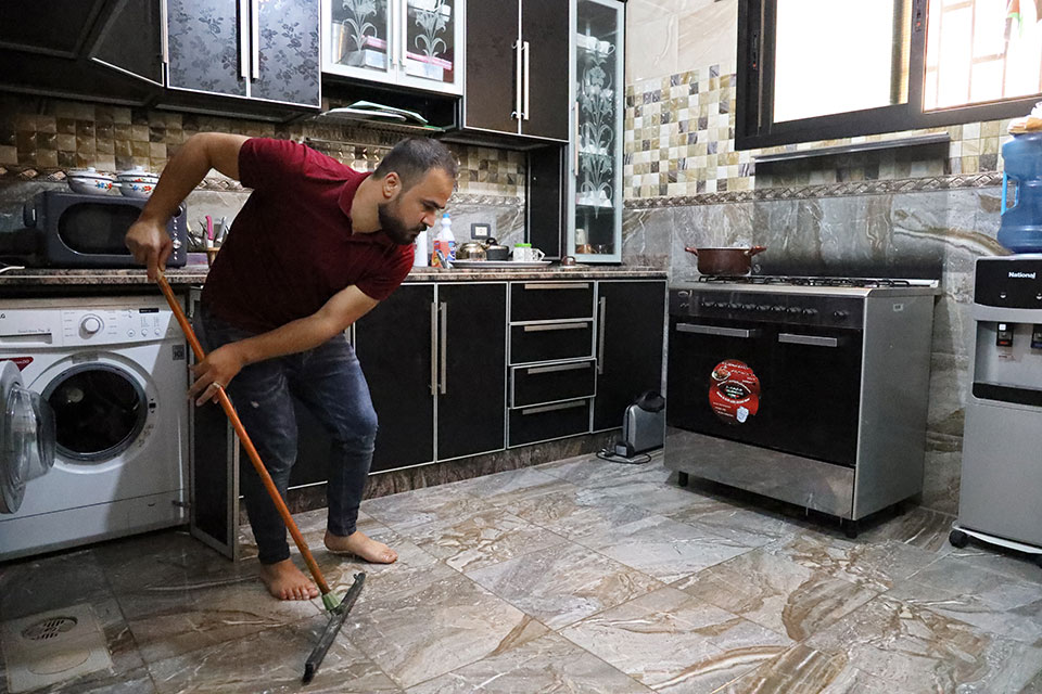 Mahmoud cleans the kitchen floor while his spouse Malak is at work Photo: Ramzi Haidar/Dar Al Mussawir for UN Women