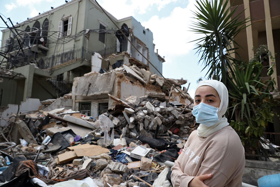 A woman in front of a destroyed house, Karantina, Beirut. August 9, 2020. Photo: Dar Al Mussawir