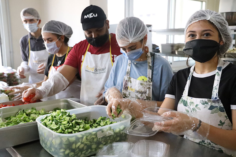 Young women and men have volunteered to cook meals for families affected by the Beirut explosion in Mairo's kitchen in Sin El Fil, Beirut. Photo: Dar Al-Musawir/Ramzi Haidar for UN Women