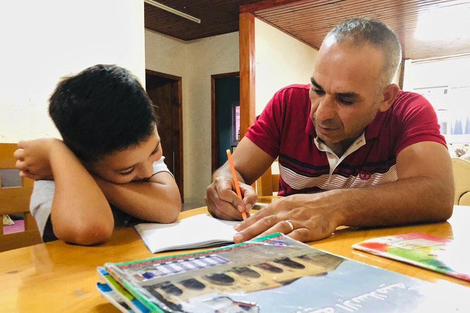 Amer Farragy helps his son Majd with schoolwork. Photos Courtesy Ilham Edaes and Amer El Farrargy