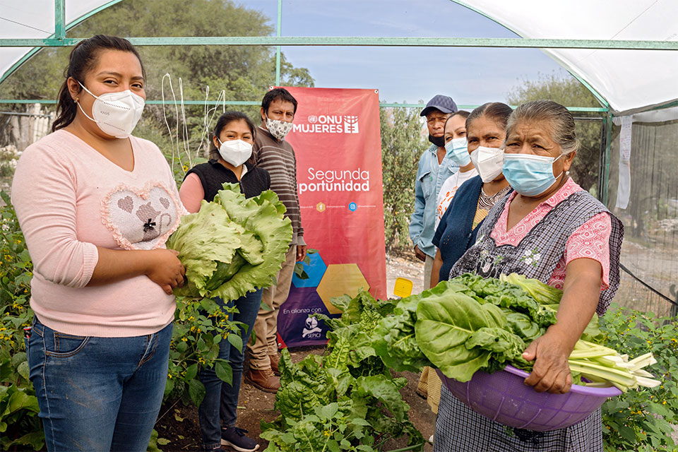 Participants from the Sembrando Esperanza (Sowing Hope) module in San Cristóbal Tepeteopán  pose for a photo with vegetables from their greenhouse.  Some in the program sell the vegetables they harvest, others use the produce to feed their families. Photos: UN Women/ Dzilam Méndez