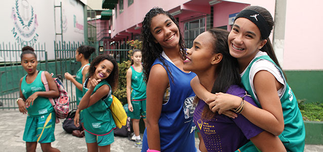Three girl participants in the 'One Win Leads to Another' in Brazil celebrate during a basketball game. Photo: UN Women/Gustavo Stephan