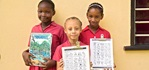Girls in Seychelles show off their worksheets on Mangroves. Photo: UN Women/Ryan Brown