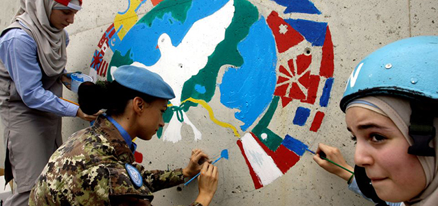 Children join an Italian peacekeeper to paint a message of hope in the southern Lebanese town of Naqura during International Day of Peace. Photo: MAHMOUD ZAYYAT/AFP via Getty Images