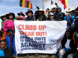 Climbers raise their flags to celebrate milestones as they make their way up Mount Kilimanjaro. (UN Women Photo)