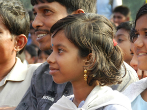 A father and daughter watch an interactive theatre performance in the field at her school in Satkhira, Bangladesh.