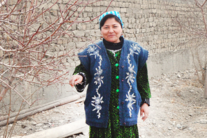 Anjira Ashurova stands in the yard outside of her home. Photo credit: Association of Women and Society