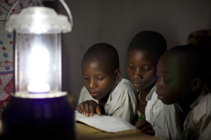 Children study in the evening thanks to a solar-powered lantern in the village of Chekeleni, southern Tanzania. Photo credit: VSO/Ben Langdon.