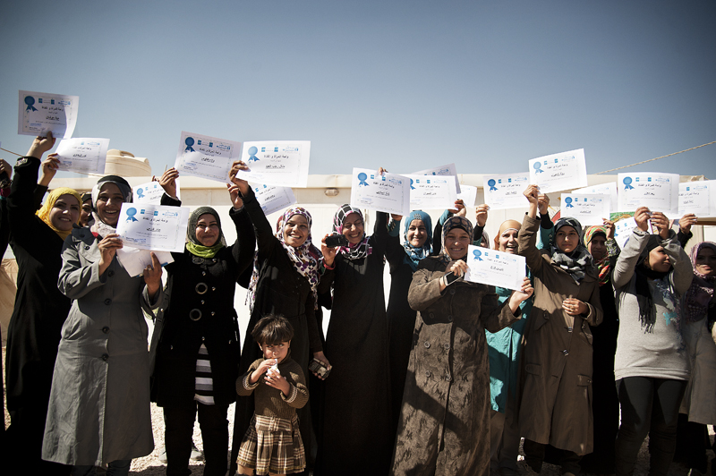 "The first Syrian women graduates of the ""Women and Girls Oasis"" programme celebrate at the Za'atari Refugee Camp in Jordan. Photo credit: Ventura Formicone"