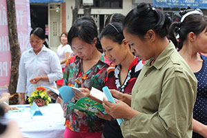 Women migrant workers read literature about their rights during the discussion on empowering migrant women with UN Women Asia-Pacific Regional Director Roberta Clarke in Ha Noi. Photo: UN Women/Thao Hoang