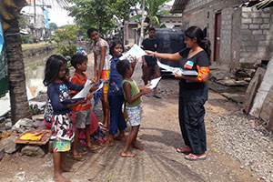 Chamathya (right) distributes lealfets for children in a low-income urban settlement in Colombo. Photo: Kavishna Thangarajh