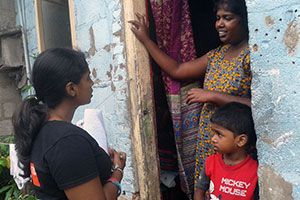 Chamathya (left) polls local families and women about their living conditions. Photo: Setavya Mudalige