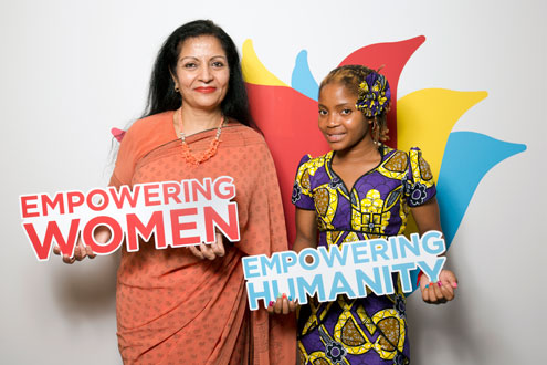 Ms. Puri and Raquelina pose in front with the logo for UN Women's Beijing+20 campaign. Photo: UN Women/Ryan Brown