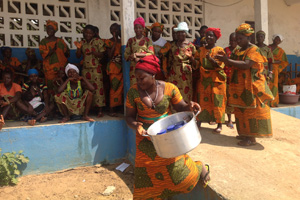 Women from across Gharpolo County, Liberia bring pots filled with the dried food and spices they produced through the project to show the visiting delegation. Photo: UN Women/James Mulbah