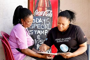 Ayda Ramatsiba Maphefo (left), woman entrepreneur and Portia Tsienyane (right), Hand-In-Hand Trainer discuss Maphefo's financial books during a follow up meeting. Photo: UN Women South Africa
