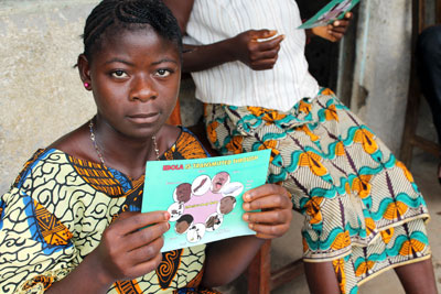 woman in Sierra Leone holding Ebola info card