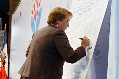 "President of Chile Michelle Bachelet signs the Call to Action, ""Women Leaders: Time to Step It Up for Gender Equality,"" during the closing ceremony of the high-level event on ""Women in power and decision-making: Building a different world,"" held in Santiago, Chile, on 27–28 February 2015. Photo: UN Women/Carolina Sainz."