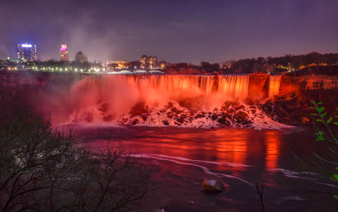 Niagara Falls, both American and Canadian Horseshoe falls, bathed in orange light on 24 November 2015. Photo: UN Women/James Neiss
