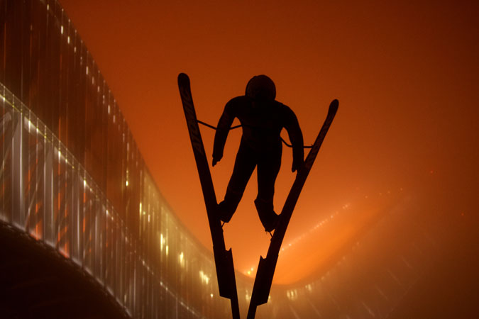 In Oslo, Norway the statue of a skier stands out against the orange-lit backdrop of the Holmenkollen ski jump. Photo: Susanne A. Finnes