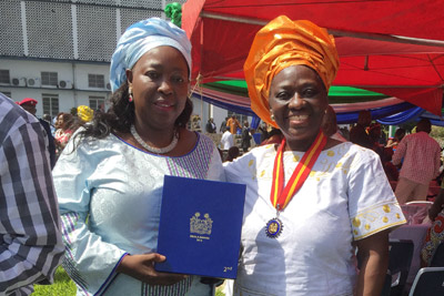 Baindu Massaquoi, UN Women Programme Specialist who was seconded to the United Nations Mission for Ebola Emergency Response during the emergency , and  Mary Okumu, UN Women Representative for Sierra Leone, accept a Silver Medal, honoring work during the Ebola crisis,  awarded to UN Women by the President of Sierra Leone on 18 December 2015 at the State House in Freetown Sierra Leone. Photo: UN Women