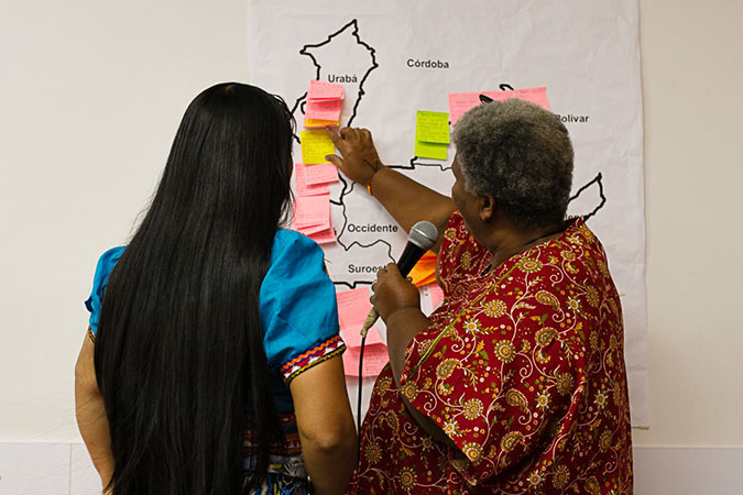Two women leaders look at a map while discussing how to support peace strategies in various communities. Photo: David Fayad