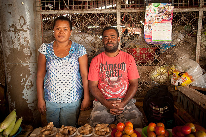 Lusiana Bulu, 38, and her husband Lukekalevu at Ba Market in Fiji's Western Division. The cyclone was already approaching Ba when she left the market to secure her home and by that time it was too late to head to an evacuation centre. They lost their toilet and bathroom and still have no electricity. The market is their only source of income, but many customers cannot afford the higher prices caused by a shortage of local produce after Tropical Cyclone Winston. Credit: UN Women/Murray Lloyd
