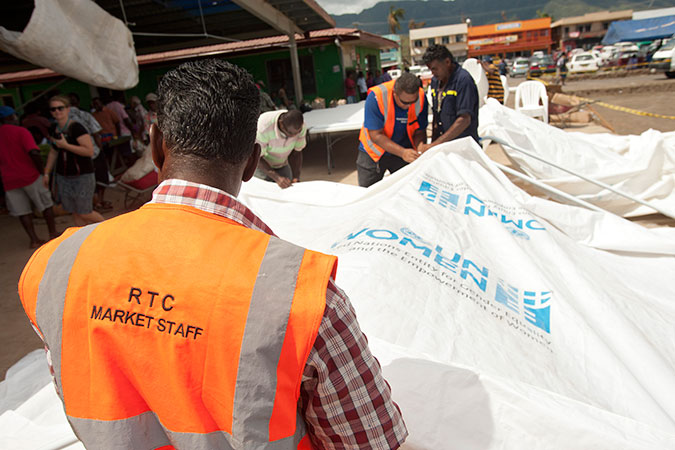 Putting up the tents, tables and chairs provided by UN Women to serve as a temporary market space in Rakiraki. Tropical Cyclone Winston destroyed the market building, depriving hundreds of vendors, most of them women, of a place not only to earn a living, but also to support each other emotionally as they recover. The tents, tables and chairs were provided through UN Women's Markets for Change project, which is funded by the Australian Government. Credit: UN Women/Murray Lloyd